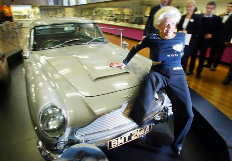 "Honor Blackman sur le capot de l'Aston Martin DB5 de James Bond lors de l'ouverture de l'exposition ""Bond, James Bond"" au Science Museum de Londres le 15 octobre 2002"